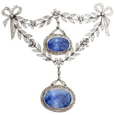 Belle Epoque Certified Ceylon Sapphire and Diamond Brooch Pin. Fairy Unheated Ceylon Sapphire and Diamond brooch from the Belle Epoque ear. Circa 1905. In the garland style, designed as a tied ribbon bows with scrolls and articulated floral swags, featuring two sapphire and diamond set drop pendants. The larger sapphire measures 15.7 x 11.1 x 7.57 mm, approx. 10.55ct, and the smaller is 13.2 x 8.5 x 7.58 mm, approx. 6.80 ct. The two sapphires together: 17.35 ct