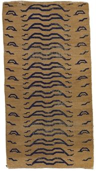 A tiger rug Tibet, 19th century Woven with navy blue undulating stripes on a honey-gold ground 64¼ x 34¼ in. (163 x 87 cm.)