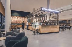 Industrial interior design with a concrete floor by Stone Age at Starbucks, University of Twente. Starbucks, Industrial Interior Design, Stone Age, Cafe Design, Concrete Floors, Retail Design, Flooring, Table, Furniture
