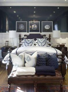 navy blue coastal bedroom design with glossy navy blue walls paint color, black bed, tapered glass lamps, black wood nightstands, brown leather tufted bench with nailhead trim and blue & white pillows and art! white blue bedroom colors. crieke33