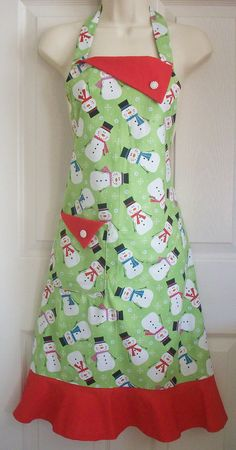 This cute Christmas apron is a colorful motif of happy snowmen wearing top hats and winter scarves and tumbling topsy turvy on a background of apple