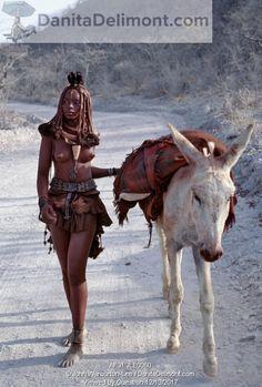 Himba woman drives home her donkey along dusty white tracks.