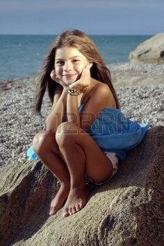 Little girl in a sunset light sitting on a rock on a beach