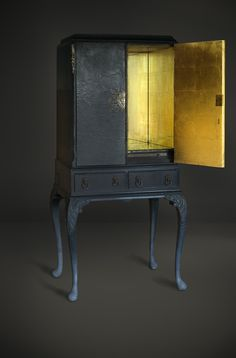 Fabulous medium sized drinks cabinet, blue black with leather finish to the doors and original hardware. Interior gold leafed, mirror and glass and antique lin