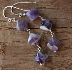 Large, diamond shaped, amethyst stones are wrapped with sterling silver wire in these long dangle earrings. Each earring consists of three 13mm x13mm (1/2 x 1/2) faceted, diamond shaped amethyst beads with stripes and swirls of purple, lilac and white combined. The total length is 2 5/8