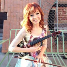 Lindsey Stirling smiling and being  confident makes you more beautiful, I feel happy being her fan I feel happy that I listen to her music and see her smile from of the photographic which is cute.