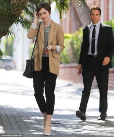 Effortlessly chic: The Love, Rosie star strutted her stuff in a pair of towering nude and white Mary Jane heels, which she teamed with elegant black cigarette pants