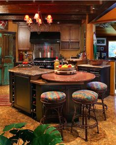 This open-plan kitchen in North Carolina features rustic and country elements, including a pair of reclaimed wood doors partially painted green, bronze and copper metallic finishes, and black painted cabinetry.