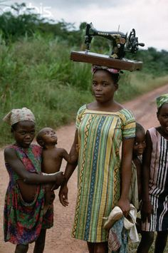 Woman carrying sewing machine on her head