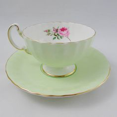 Green tea cup and saucer made by Aynsley. On the inside rim of the teacup there are pink roses. Gold trimming on the edges of tea cup and saucer and on the handle. Excellent condition (see photos). Markings read: Aynsley England Bone China For more Aynsley tea cups, please click