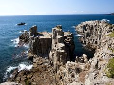 """The series of spectacular rugged cliffs called Tojinbo are almost 100 feet tall and have been designated one of Japan's natural monuments. The tall rock pillars were first formed by """"columnar jointing"""" as a result of volcanic activity, and have been shaped by the tumultuous waves of the Sea of Japan."""