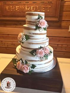 Wedding cake loveliness! A naked style wedding cake with artificial flowers on a dark wood cake stand. Yes, fake flowers! Don't they look real!?! #weddingcakes