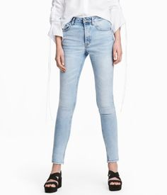 Light denim blue. 5-pocket, ankle-length jeans in washed stretch denim with distressed details. High waist, button fly, and skinny legs.