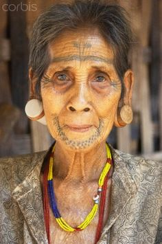 Laos | Portrait of facially tattooed woman.  Champasak, Bolaven Plateau | © Ian Trower
