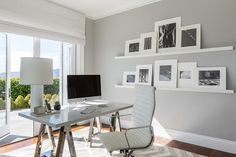 Chic, sleek office features a chrome sawhorse desk and an Eames Management Chair placed atop a white and gray herringbone rug placed in front of stacked side by side picture ledges.
