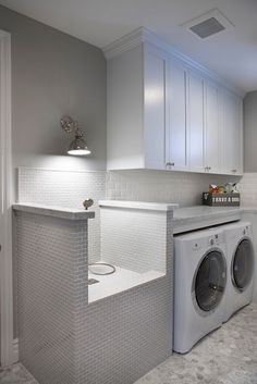 This stunning laundry room features white cabinets and a very practical pet shower and grooming station. Flooring is hex marble tiles.