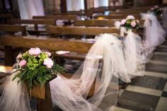 Wedding flowers and decorations in the aisle of the church: tulle, pink peonies and green hydrangea