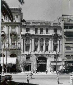 """""""Η πρώτη εκδοχή του κτηρίου Νικολούδη στην οδό Πανεπιστημίου, [σημ. όπως απεικόζεται στην φωτογραφία] για την οποία δεν υπάρχουν πλήρη στοιχεία, σχεδιάσθηκε το 1897 από τον ίδιο τον αρχιτέκτονα Αλέξανδρο Νικολούδη, σπουδαστή ακόμα της Ecole des Beaux-Arts στο Παρίσι. Old Photos, Vintage Photos, Old Greek, City People, Greek Culture, Acropolis, Athens Greece, Neoclassical, Historical Photos"""