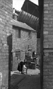A cramped courtyard, overshadowed by factories, off Mansfield Street in the early 1930's. These houses had no inside toilets and no sink indoors. All the washing had to be done outside. These slums were situated close to today's bus station in Leicester. They were demolished in the early 1930's.