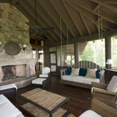 i love screen porches! how fun to have a swing in it and a fireplace when it's chilly...