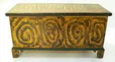 A Pennsylvania Smoke Decorated Blanket Chest.  Pine, circa 1820-40, original chrome yellow paint with smoke decoration at the sides and lid. The case is raised on the original straight bracket feet, the moldings are painted dark green. The backboard has an illegible inscription in pencil, apparently a name and date. locatiauctions.com