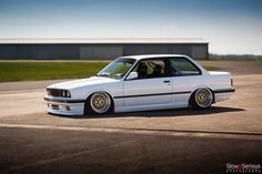 White & classic BMW E30. Lowered with golden rims.