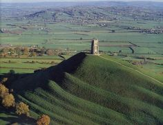 (Glastonbury Tor) Glastonbury is built on high ground surrounded on all sides by the Somerset Levels. In the Dark Ages, however, the Levels were marshland and Glastonbury stood proud as an island towering above them. The Tor, that dominates the countryside around Glastonbury, is said to be the entrance to Annwfn/ or Avalon, The Celtic Underworld. this is where a Celtic King, such as Arthur, would go when near to death.