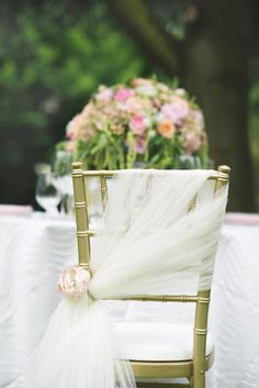 Wedding Chair Ideas — Here's another ModWedding reception idea.This Chiavari chair is diagonally draped with organza. Instead of a bow, a single flower bundles the fabric together.