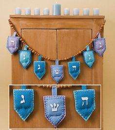 Homespun Hanukkah Garland @J O-Ann Fabric and Craft Stores: Dreidel shapes cut from four shades of blue fleece are sewn around the edges with embroidery floss using a decorative blanket stitch to create a plush holiday garland for Hanukkah. Project courtesy of Jo-Ann Fabric & Craft Stores. (Download the free Project PDF)