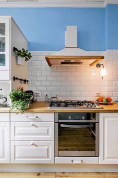 Do stylu kuchni starannie dobrano sprzęt AGD (okap z drewnianą ramą, płytę gazową z dużymi rusztami i pokrętłami) oraz dodatki - relingi, ceramiczne gałki i uchwyty szafek. Swojski klimat podkreślają doniczki z ziołami.
