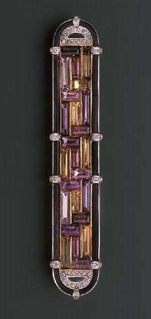 AN ART DECO DIAMOND AND GEM-SET BAR BROOCH, BY CARTIER. The central geometric panel of buff-topped amethyst, garnet, pink sapphire and citrines to the rose-cut diamond half-moon terminals within a border of elephant hair and diamond detail, late 1920s, Signed Cartier London.