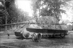 """Little Boy in front of German Tiger II Tank that awaits scrapping - Germany, 1945 Roflkopt3r: """"Small boy, absolutely massive tank. Here is a Tiger II with a soldier for scale. Here another one with a group. """""""