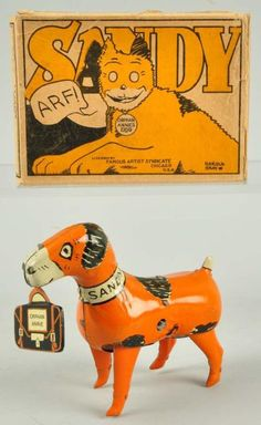 "1930's Sandy Tin Litho Wind-Up Toy. This toy is marked ""Sandy"" around neck area and is holding suitcase marked ""Orphan Annie"". Suitcase is a replacement. Includes original box marked ""Orphan Annie's Dog Licensed by Famous Artist Syndicate Harold Gray"". Box is complete and has nice depictions of dog on both sides."