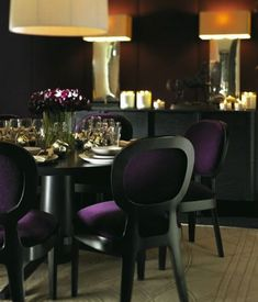 Purple & black dining room design with linen round pendant lighting, purple, upholstered dining chairs, round black dining table, box pendant lights above the black buffet finish the room. Purple black cream beige brown dining room colors. Purple paint wall color.