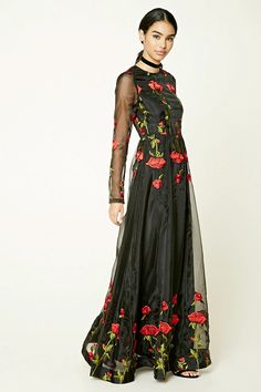 A mesh maxi dress featuring an embroidered floral applique design, a high neckline, long sheer sleeves, knit underskirt, and a concealed back zipper.