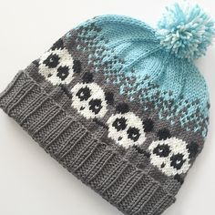 Pandamonium is a hat knit in the round from the bottom up. The hat starts with a 2x2 rib and then continues with an adorable panda colorwork pattern. This whimsical hat continues with an ombre effect as the color changes from one shade to another. #FreePattern