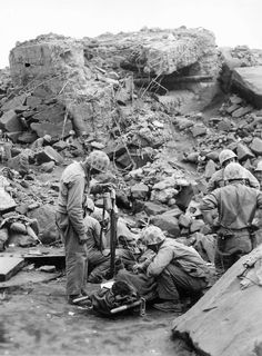 Battle of Iwo Jima, 1945: US Marine corpsmen come to the aid of a wounded comrade against the backdrop of a smashed up Japanese pillbox. The barrel protruding out of the pillbox is a Japanese 120mm AA gun Type 3.