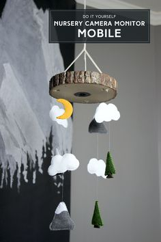 How cool! Hide the baby camera in your nursery in a mobile! This DIY nursery mobile tutorial shows how to incorporate a camera into a wood slice top as well as how to make a woodland mobile made of felt mountains, clouds, and trees. The DIY nursery camera mobile is a fun DIY project and would be a great addition the nursery.