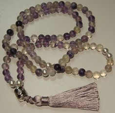 Fluorite #Mala. 108 beads. Purple, lavender & clear fluorite with a few faux silver pearls. Finished with 2 small accent borealis beads, silvertone barrel bead, and silky tassel. Bead size is 8mm 