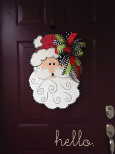 Welcome guests with this whimsical hand painted Santa door hanger. It measures 24 tall x 16 wide, sprayed with an acrylic top coat and