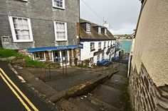 Stairway down to the sea and shops that front the bay in Saint Mawes, Cornwall, England