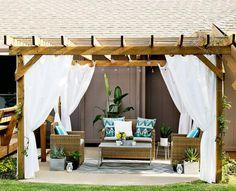 pergola en bois autoportée décorée de rideaux blancs et coussins à motifs turquoise et aménagée avec un salon de jardin en rotin