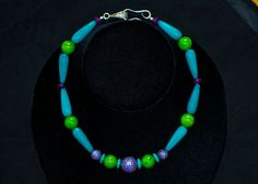 Natural stone choker necklace made with, green and aqua jade, turquoise roundels and a pave set purple cz ball with a sterling silver clasp....