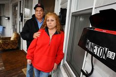 Isabel and Juan Muneton pose next to their mailbox for their apartment, Thursday, Nov. 6, 2008, in Lawrence, Mass. A bank recently gave notice to the couple to move out because of a foreclosure, even though their landlord never informed them. The couple has a Neighborhood Legal Services lawyer on their case and they remain in the apartment. (AP Photo/Lisa Poole)