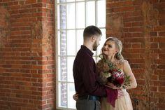 bride and groom posing in front of window