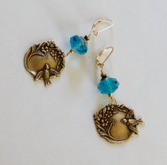 Indicolite blue Swarovski crystal rondels with brass ox bead caps and flying bird with flowers, on 14k gold-filled hooks. by ChrisAllenJewelry on Etsy