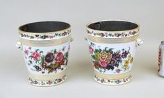 "Pair of French Vieux Paris porcelain cache pots on stands with tin liners. Gilt wear, loss; base chip to one cache pot, one with interior hairline cracks to base, both stands with restoration. Approximately 7 1/2"" high, 8"" wide."
