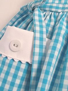 Sleeveless dress made in very fine poplin gingham with white pique collar and pockets edged with white ric-rac. Narrow ties at the sides and back buttons. Fully lined with cotton lawn.