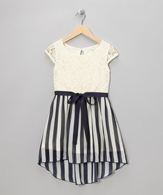 This dress is a mix a fashion maven will love with its unexpected vertical stripes complementing the light lace top. A flowing ribbon gives this piece an extra spot of special.First and third shell: 100% polyesterSecond shell: 95% nylon / 5% spandexHand wash; dry flatImported