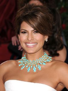 A white dress is perfectly accentuated on Eva Mendes, with a beautiful turqoise or aqua stoned neck embellishment.